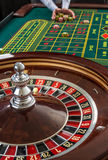 A roleta e as pilhas do jogo lascam-se em uma tabela verde Fotos de Stock