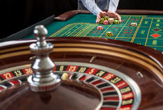 A roleta e as pilhas do jogo lascam-se em uma tabela verde Fotografia de Stock Royalty Free