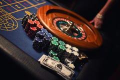 Roleta, microplaquetas e dinheiro no casino Conceito de jogo imagem de stock