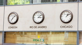 Rolex Showcase with clocks on the wall with time zones. Royalty Free Stock Photo