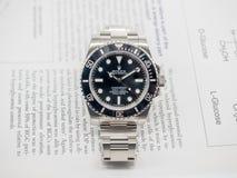 Rolex submariner on English paper Stock Photo