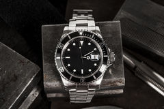 Rolex Submariner Watch. Close up of a Rolex Submariner watch on old steel tools Stock Photo