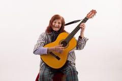 Rolig äldre dam som spelar den akustiska gitarren royaltyfria bilder