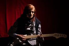 Rolig äldre dam som spelar den elektriska gitarren arkivfoto