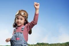Rolig asiatisk liten flicka i flygarehatt och skyddsglasögon som spelar på fi Royaltyfri Fotografi