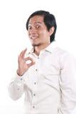 Rolig asiatisk man som visar det reko tecknet Arkivfoto