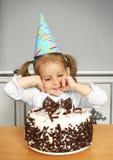 Rolig barnflicka med den födelsedaghatten och kakan Arkivbilder