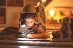 Rolig barnflickaturist med ficklampan och världskarta och backp Arkivfoton