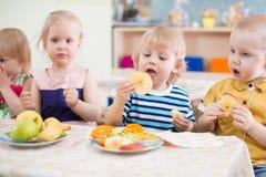 Rolig barngrupp som äter frukter i dinning rum för dagis royaltyfri fotografi