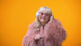 Rolig barnslig åldrig dam i gullig dräkt som låtsar för att vara discjockey, hobby och drömmar arkivfilmer