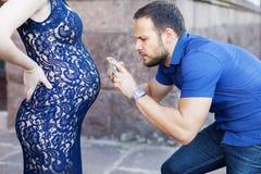 rolig bild Man som fotograferar den gravida buken på telefonen Arkivfoto