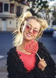 Rolig blond flicka i rosa exponeringsglas som rymmer lolliop Arkivfoto