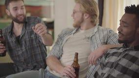 Rolig caucasian för stående två och män för en säkra afrikansk amerikan som sitter på soffan Tre män som tillsammans sitt lager videofilmer