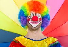 Rolig clown på en färgrik bakgrund Fotografering för Bildbyråer
