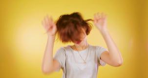 Rolig dans för flicka för brunett för Ð-¡ ute och att tycka om segern, flytta sig som är roligt som ler på gul bakgrund Seger sho arkivfilmer