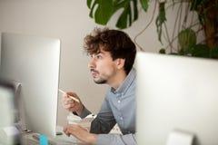 Rolig förvånad anställd som äter kinesisk mat som ser datoren arkivfoton