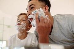 Rolig fader och son som rakar i badrum royaltyfri fotografi
