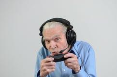 Rolig farfar som spelar en videospel på konsolen arkivbild