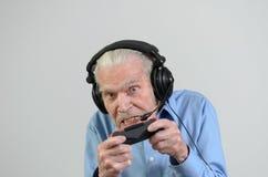 Rolig farfar som spelar en videospel på konsolen Royaltyfria Bilder