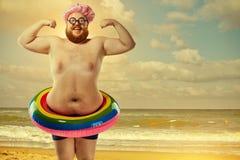 Rolig fet man i en baddräkt med en uppblåsbar cirkel på beaen Royaltyfri Foto