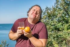 Rolig fet man på havet som dricker fruktsaft och äter frukter Semester, viktförlust och sunt äta royaltyfria bilder
