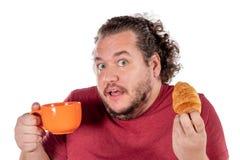 Rolig fet man som äter den lilla gifflet och dricker kaffe från den stora orange koppen på vit bakgrund Bra morgon och frukost royaltyfri foto