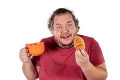 Rolig fet man som äter den lilla gifflet och dricker kaffe från den stora orange koppen på vit bakgrund Bra morgon och frukost royaltyfria bilder