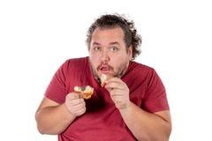 Rolig fet man som äter den lilla gifflet på vit bakgrund Bra morgon och frukost royaltyfria bilder