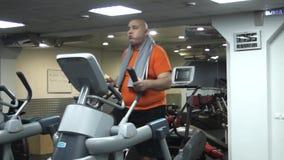 Rolig fet man som gör övningar på ellipsoiden i idrottshall stock video