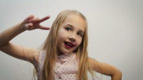 Rolig flicka, barn, blondin i en ljus skjorta med en rosa ärtamodell och att utföra dansförehavanden med kroppen och händer på a arkivfilmer