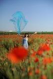 rolig flicka för blå torkduk som har vallmor Royaltyfria Foton