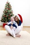 rolig flicka för jul som har henne liten mom Arkivfoton