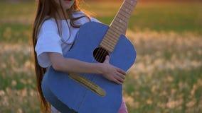 Rolig flicka för liten unge som spelar gitarren i ett maskrosfält under solnedgång utomhus i väg från stadsbyggnadssinnesrörelser stock video