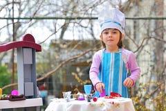 rolig flicka för matlagning som har little leka Royaltyfri Bild