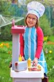 rolig flicka för matlagning som har little leka Arkivfoton
