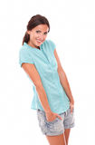 Rolig flicka i kort jeans som ser dig Royaltyfria Foton