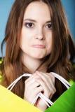 Rolig flicka med den pappers- mång- färgade shoppingpåsen Arkivbild