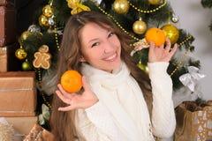 Rolig flicka med tangerin i inre jul Royaltyfri Foto