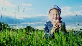 Rolig flicka som äter glass Sitter på en härlig grön äng lager videofilmer