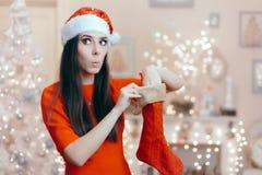 Rolig flicka som söker efter hennes gåva i en julstrumpa royaltyfria bilder