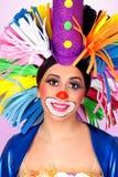 Rolig flickaclown med en stor färgrik peruk Royaltyfri Bild