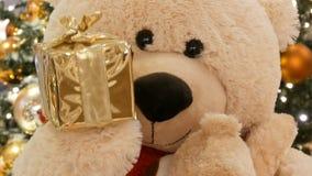 Rolig flyttning för leksaknallebjörn som rymmer i hans hand en ask med ett julgåvaslut upp Juldekor i gallerian lager videofilmer
