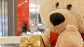 Rolig flyttning för leksaknallebjörn som rymmer i hans hand en ask med ett julgåvaslut upp Juldekor i gallerian stock video