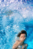 Rolig framsidastående av att le att simma för barn som är undervattens- i pöl Arkivfoto