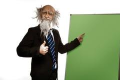 Rolig gammal lärare nära svart tavla som isoleras på vit Royaltyfri Foto
