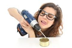 Rolig geekflicka som försöker att öppna ett tenn med en drillborr royaltyfria foton