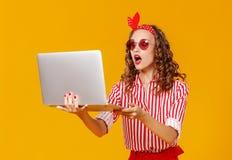 Rolig gladlynt kvinna med bärbara datorn på gul bakgrund arkivbild