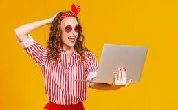 Rolig gladlynt kvinna med bärbara datorn på gul bakgrund arkivbilder