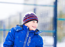 Rolig gladlynt pojke i omslaget och hatten som utomhus spelar i vinter Royaltyfri Fotografi