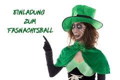 Rolig grön elakt trollvisning på tysk text för en inbjudan till ca arkivbild